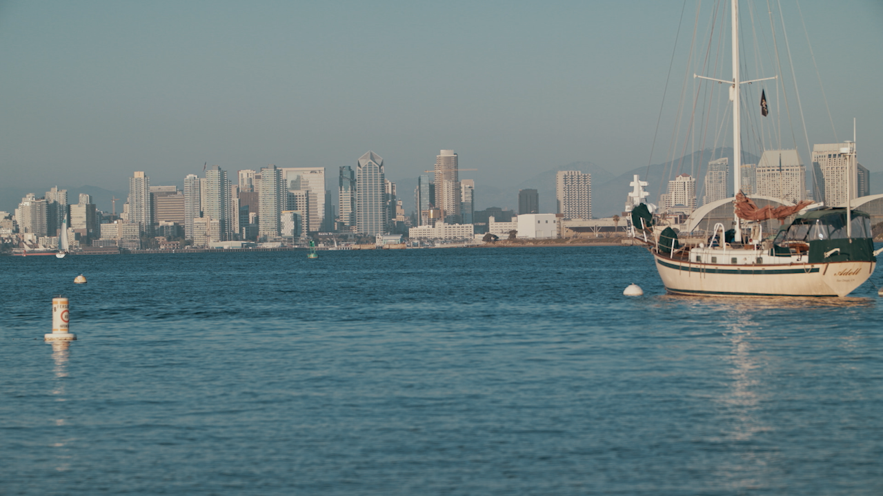 A boat floats in a bay across from a city skyline thumbnail