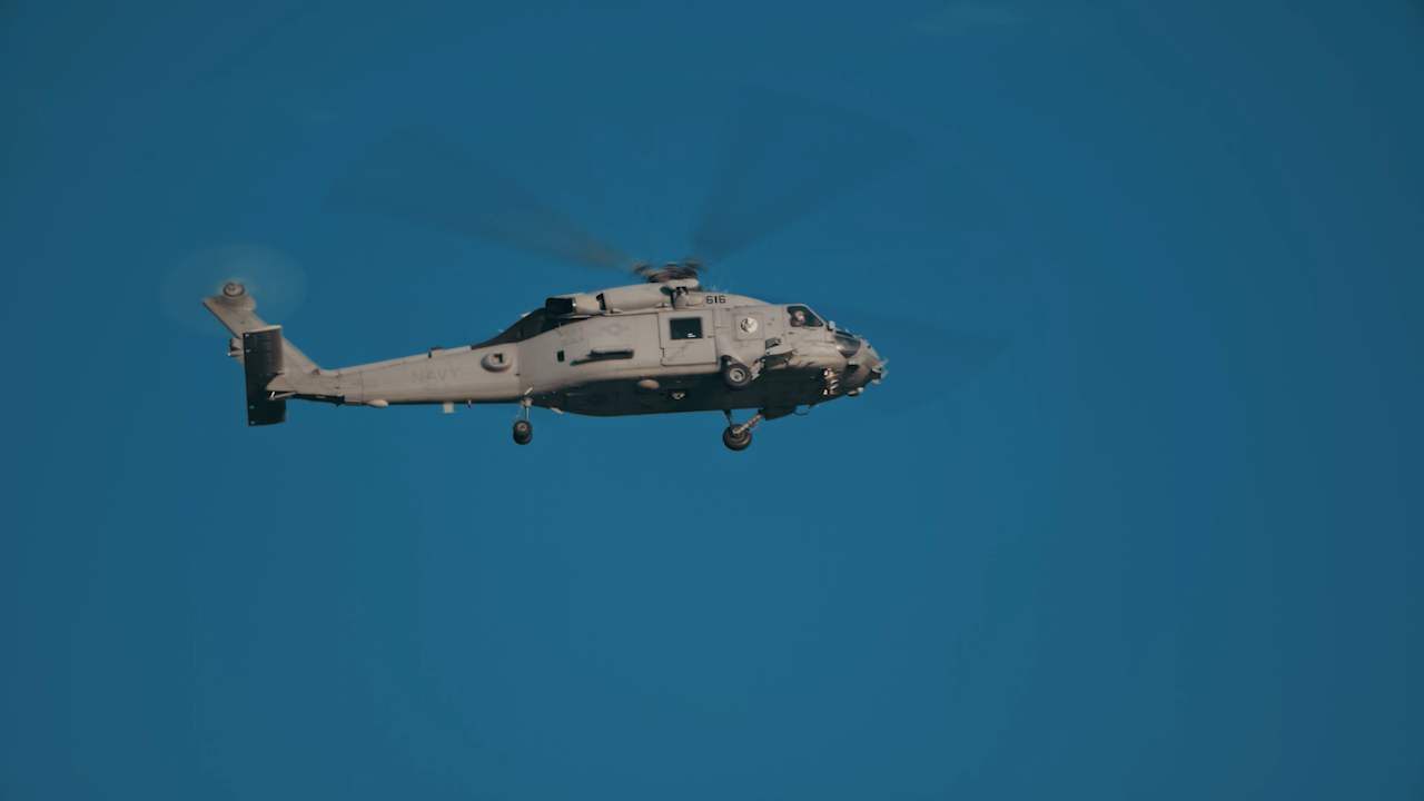 A military helicopter flies through the sky thumbnail