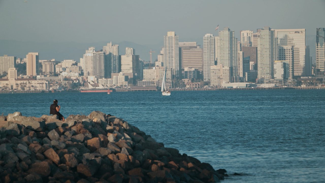 A woman sits on rocks over looking a city skyline across the bay thumbnail