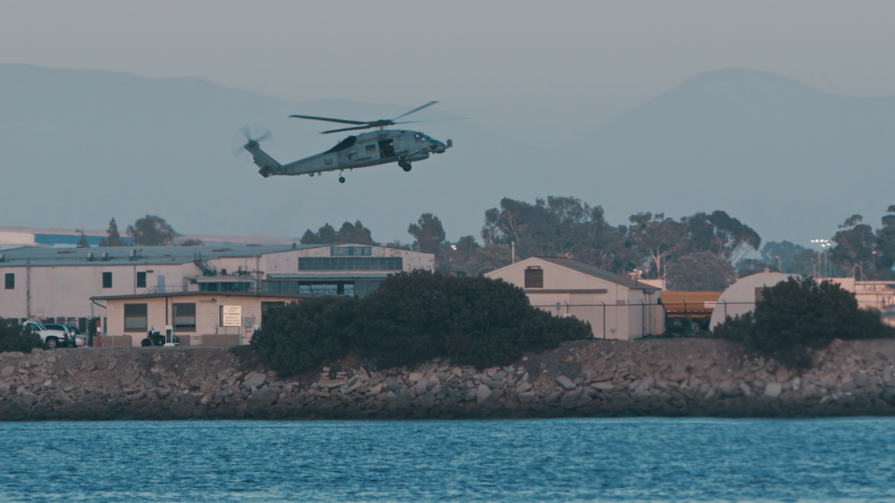 A military helicopter hovers over land and water thumbnail