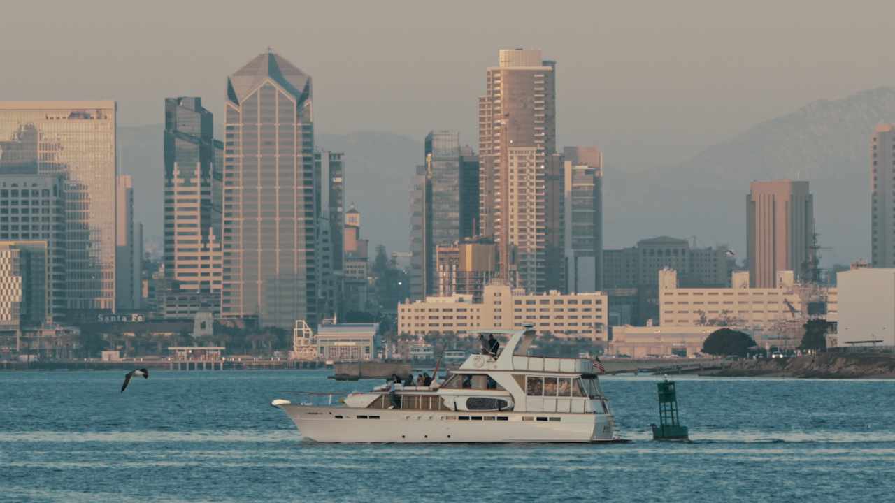 A yacht travels through a bay across a city skyline thumbnail