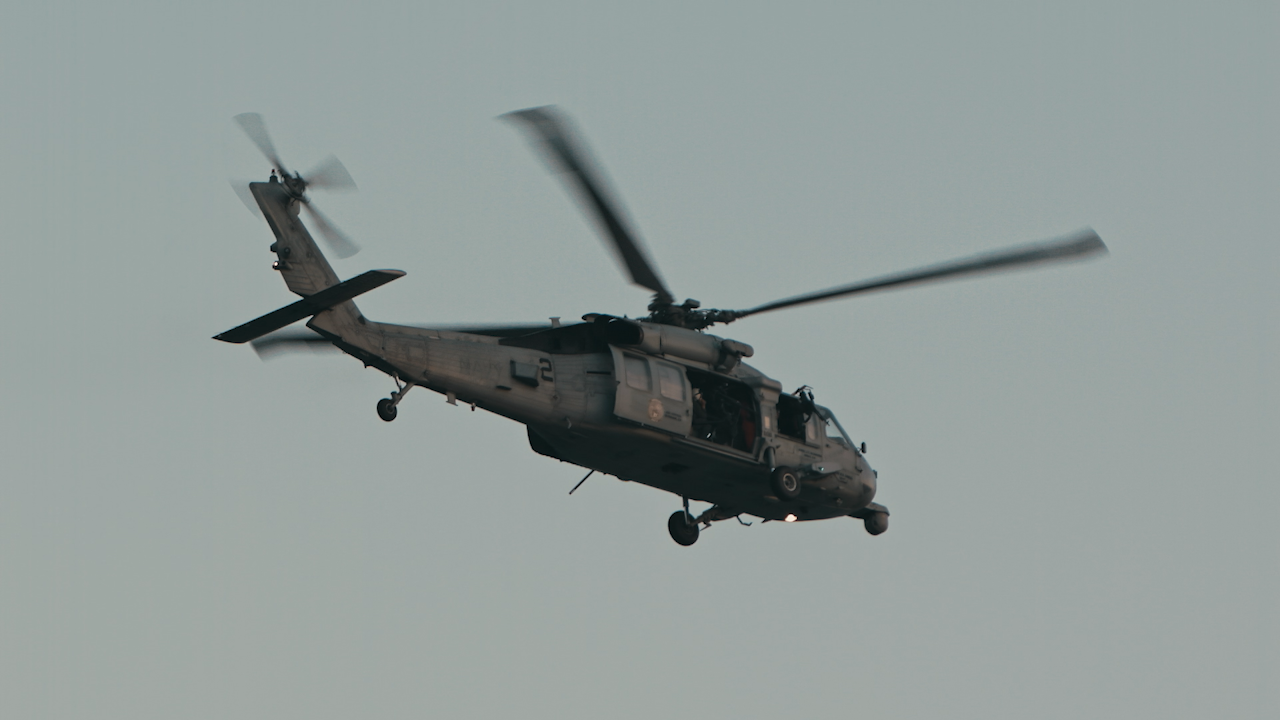 A military chopper flies through the sky thumbnail