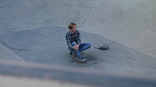 A man sits on his skateboard in a skate park thumbnail