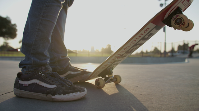 A man steps onto his skateboard and skates away thumbnail