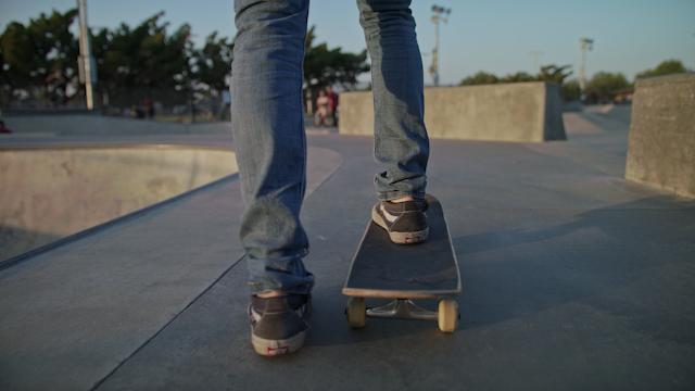 A man skates on concrete in a skate park thumbnail