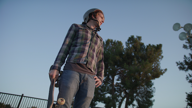 A man stands with his skateboard and looks around thumbnail