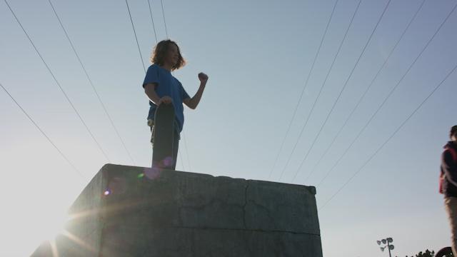 A boy stands ontop of a concrete block at a skate park thumbnail