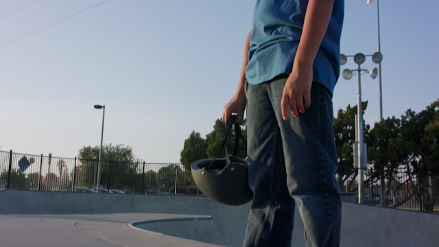 A skater is holding his helmet in a skate park thumbnail