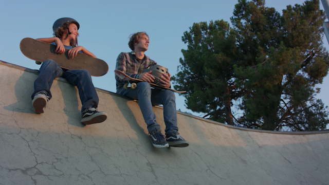 Two skaters talk and hold their skateboards thumbnail