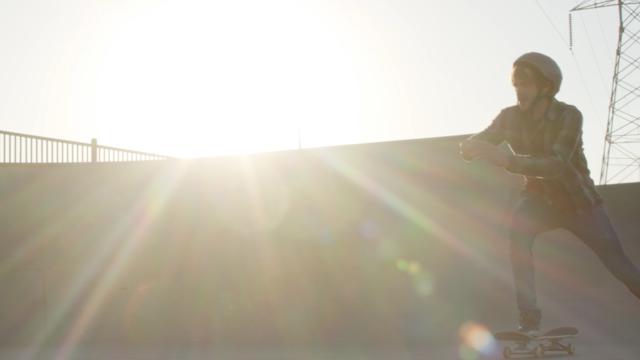 A man skates through the sunlight thumbnail