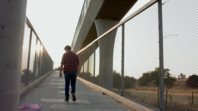 A teenage boy walks up a ramp at sunset thumbnail