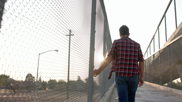 A teenage boy runs his fingers along a chainlink fence at sunset thumbnail