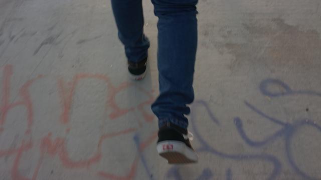 A teenage boy walks along a concrete ground thumbnail