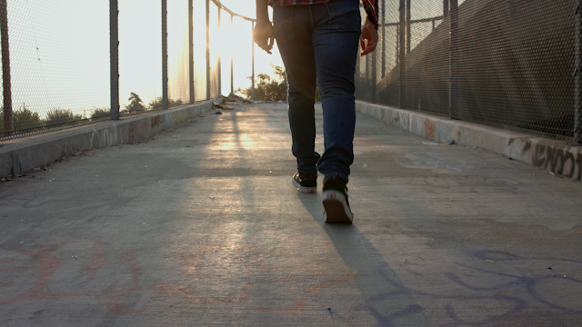 A teenage boy walks up a ramp into the sunset thumbnail