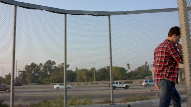 A teenage boy walks up a ramp of an overpass thumbnail