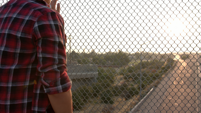 A teenage boy looks into the sunset on a freeway overpass thumbnail