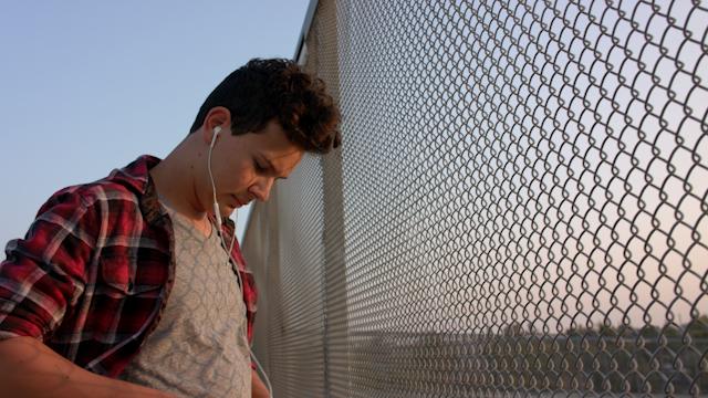 A teenage boy listens to music on an overpass thumbnail