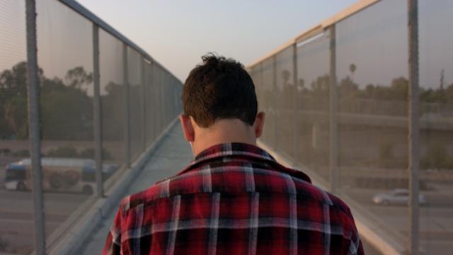 A teenage boy is walking across an overpass listening to music thumbnail
