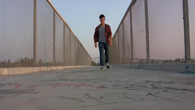 A teenage boy walks down an overpass listening to music thumbnail