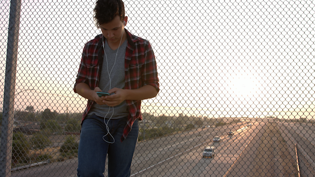 A teenage boy leans against a chainlink fence listening to music thumbnail