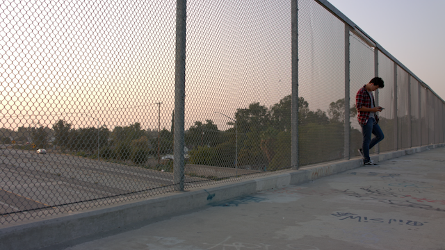 A teenage is standing on an overpass at sunset thumbnail