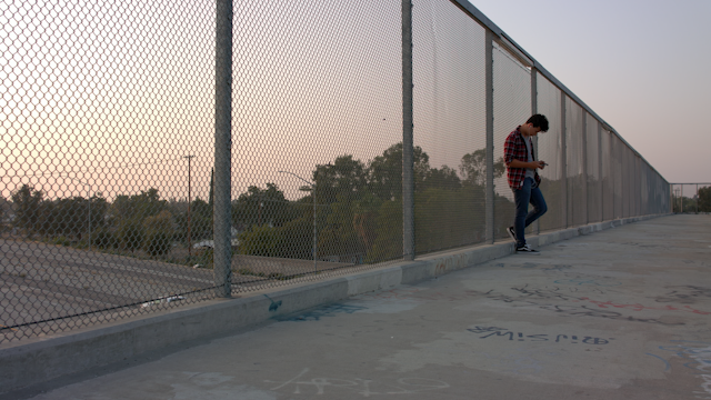 A teenage boy leans against a chainlink fence while listening to music thumbnail