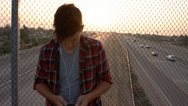 A teenage boy stands on an overpass and listens to music thumbnail