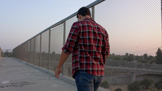A teenage boy walks across a freeway overpass during sunset thumbnail