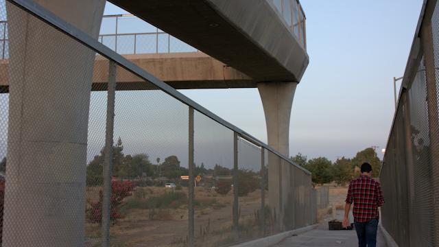 A teenage boy walks down a freeway overpass ramp thumbnail