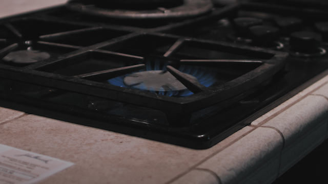 A pot is placed on a lit gas stove thumbnail