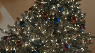A christmas tree is decorated with ornaments lights and a star thumbnail