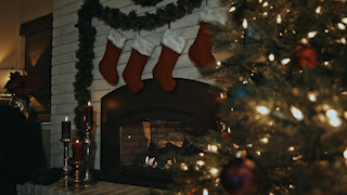Stockings hang over a fireplace with a christmas tree in the foreground thumbnail