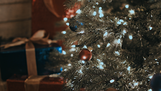Christmas presents are stacked near a decorated christmas tree thumbnail