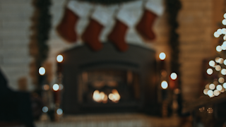 Stockings are hanging over a fireplace with candles and a christmas tree thumbnail