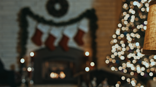 A room is decorated for christmas with a christmas tree, stockings, fireplace, lights and candles thumbnail
