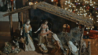A nativity scene sits on a coffee table with a bible in the foreground thumbnail