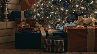 A number of presents are stacked under a christmas tree thumbnail