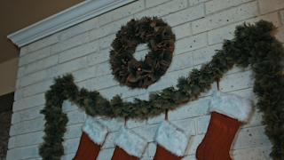 Christmas decorations and stockings hang over a fireplace with candles thumbnail