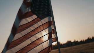 The american flag waving against sunset sky thumbnail