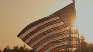 The american flag waves in front of the setting sun thumbnail