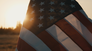 The american flag waves at sunset thumbnail