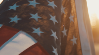 The american flag waves in the wind at sunset thumbnail
