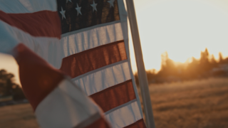 The american flag waves in a field at sunset thumbnail
