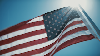 The american flag waves against a blue sky thumbnail