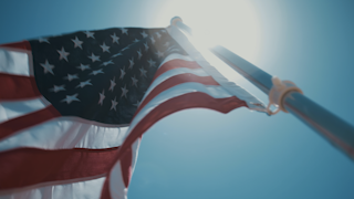 The american flag waves against a blue sky and sun flares thumbnail