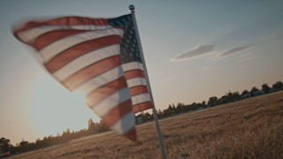 American flag is waving in field at sunset thumbnail