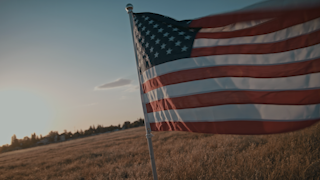 American flag waving in the wind at sunset thumbnail