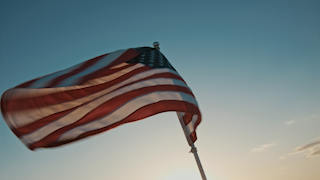 American flag blowing in the wind at sunset thumbnail