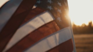 American flag waving in front of a sunset thumbnail