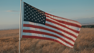 American flag waving over land at sunset thumbnail